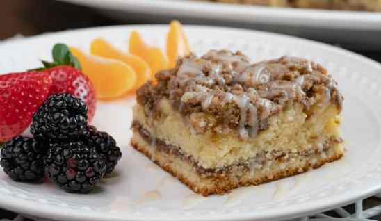 sliced coffee cake with drizzle on a white plate with blackberries, strawberries and mandarin oranges.