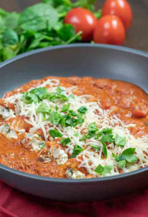 chicken and spinach skillet manicotti topped with cheese and diced spinach