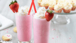 strawberry ice cream milkshake in tall glass with whipped cream red straw and garnished with a fresh strawberry.