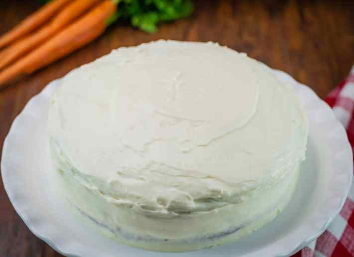carrot cake with cream cheese frosting with whole carrots in background