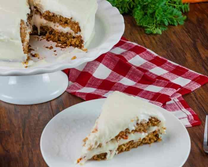 round carrot cake with cream cheese frosting with slice taken out of it and sitting on white plate with red and white napkin and fork