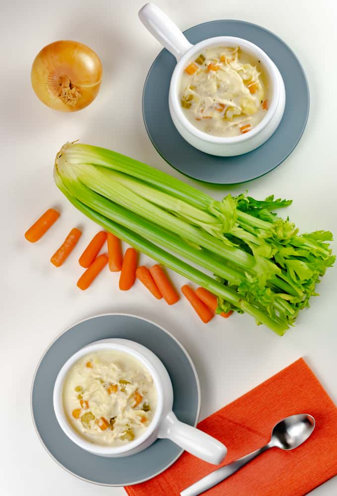Instant Pot Chicken Tortellini Soup in white bowl with handle and orange napkin