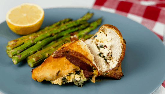 Instant Pot Stuffed Chicken Breast wrapped in bacon and served with asparagus