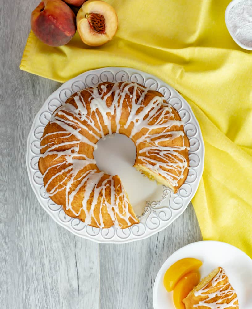Peach Sour Cream Pound Cake with vanilla drizzle on a gray background and yellow napkin.