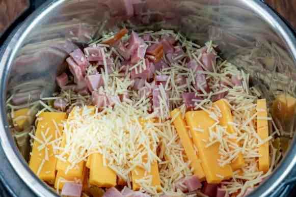 Instant Pot farfalle pasta cooked with cheddar cheese, parmesan cheese, and diced cooked ham