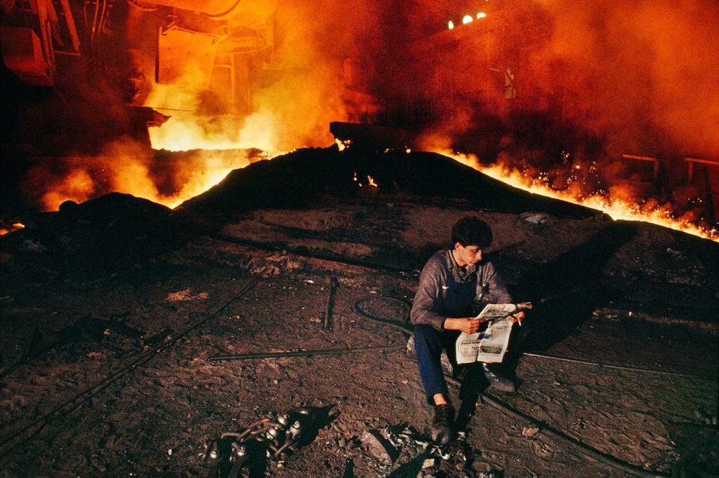 steve mccurry ragazzo legge giornale fuoco