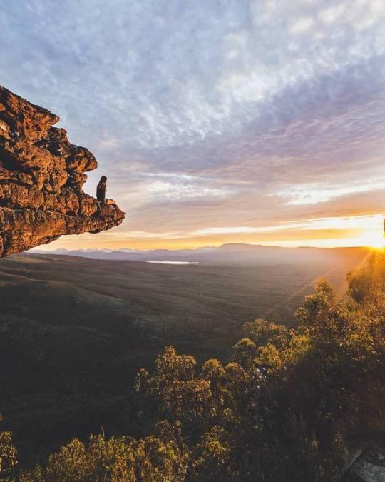 woman sitting on cliff enjoying sunrise