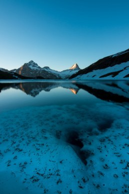 cold and clear mountain lake with snow