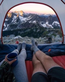 man and woman enjoying mountain view from tent