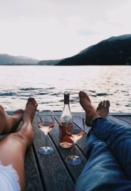 man and woman relaxing by lake drinking wine