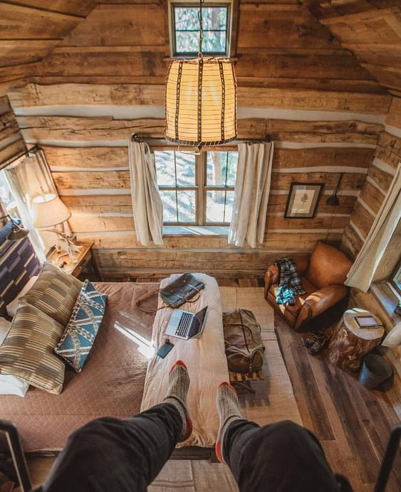 man dangles feet from balcony looking down on rustic bedroom