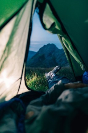 man relaxing with feet out of tent