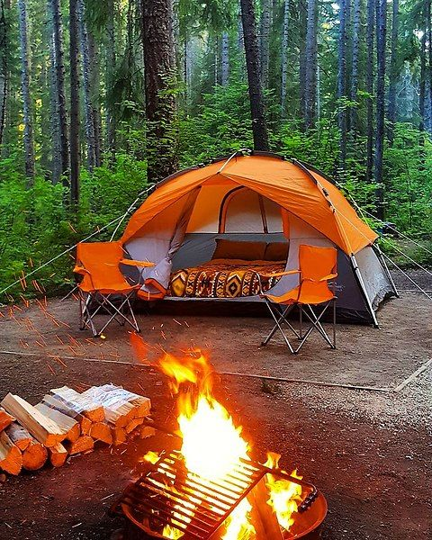 orange tent next to campfire