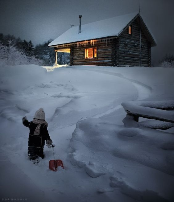 child sledding outside of cabin