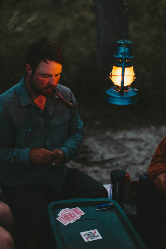 man smoking pipe while camping