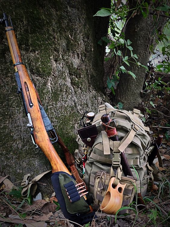 survival gear with backpack ax and rifle