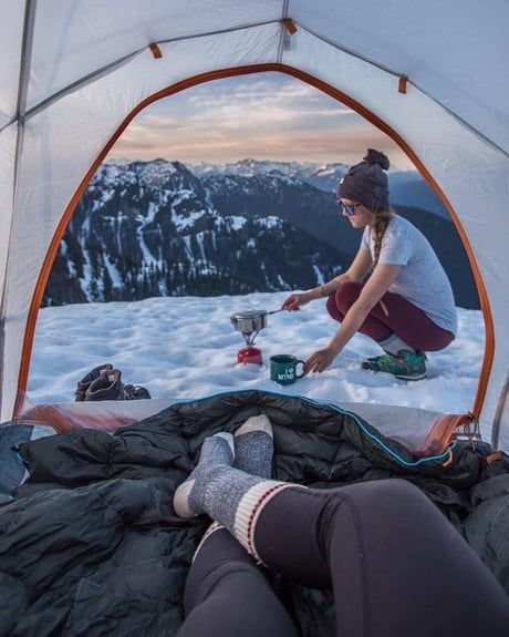couple camping on snow covered mountain