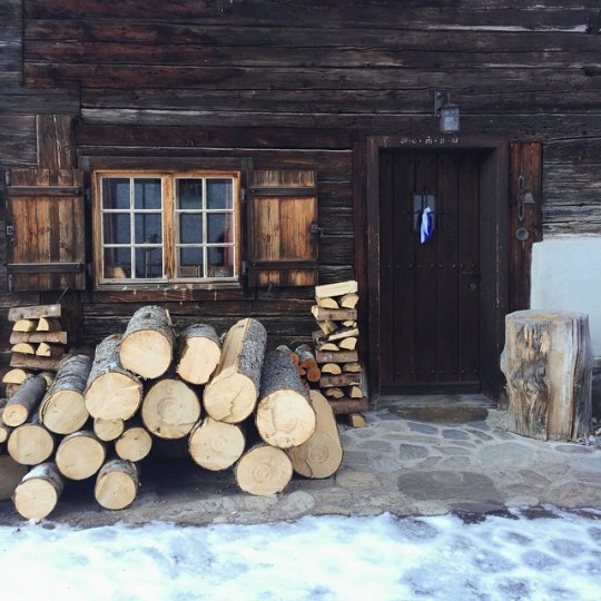 firewood stacked in front of cabin