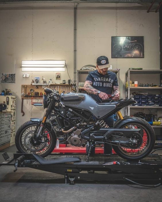 man working on motorcycle in shop