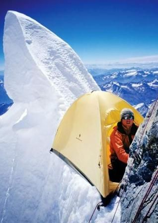 mountain climber on mountain with tent