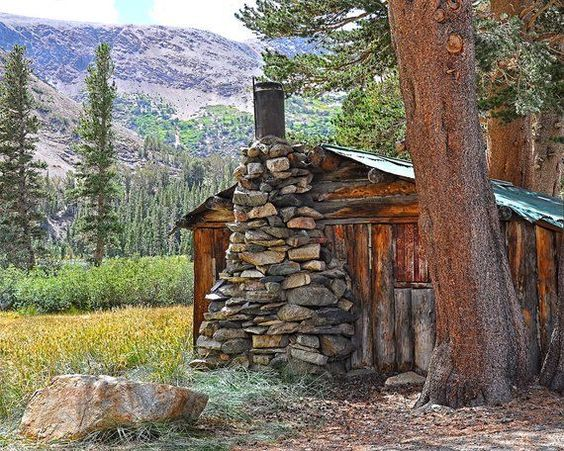 rugged and rustic little wood cabin with stone fireplace