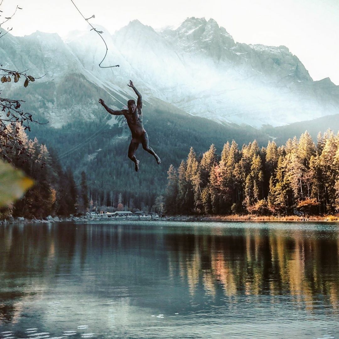 man swinging into lake