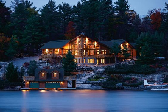 Lakeshore log cottage mansion with airplane and boathouse