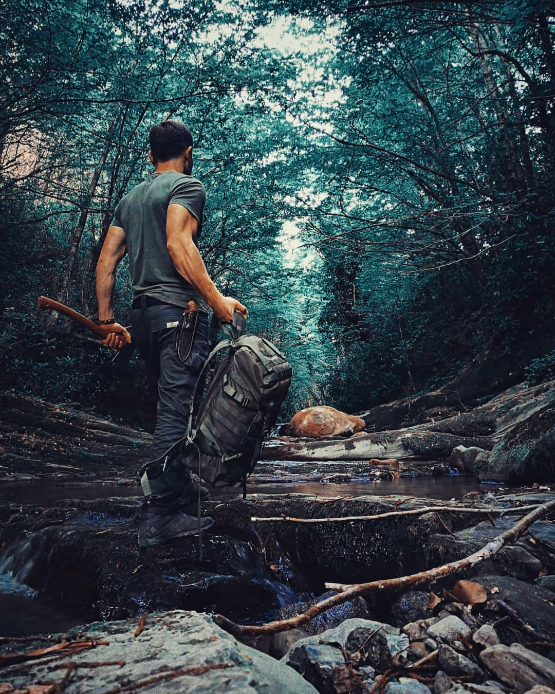 man walking through forest carrying survival gear