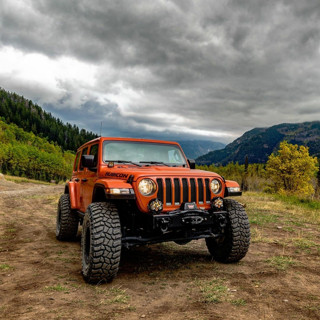 orange jeep rubicon in the country