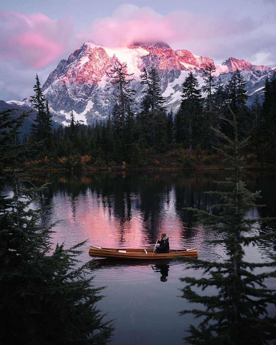 man in canoe on mountain lake