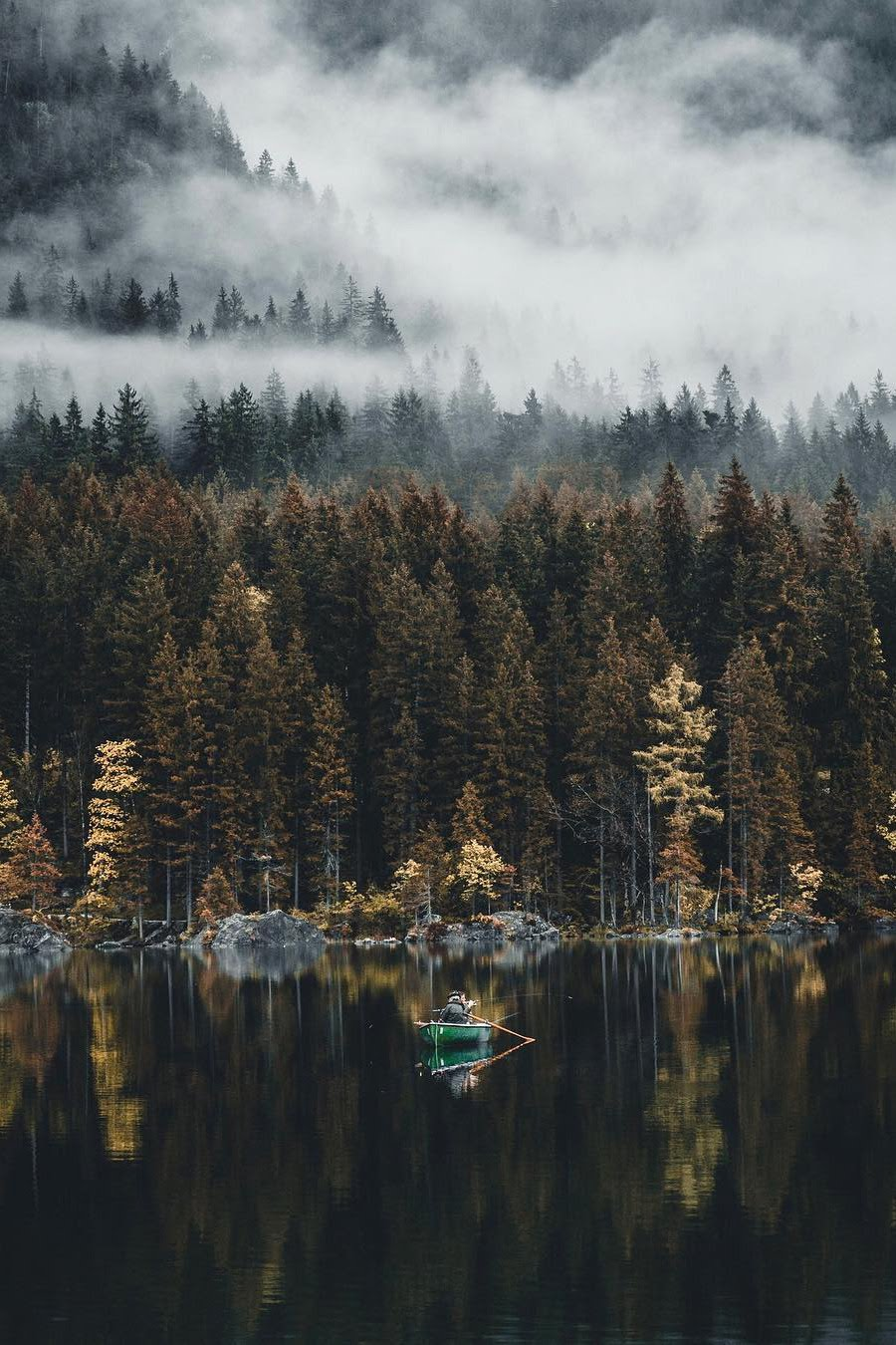 man fishing from boat on quiet mountain lake