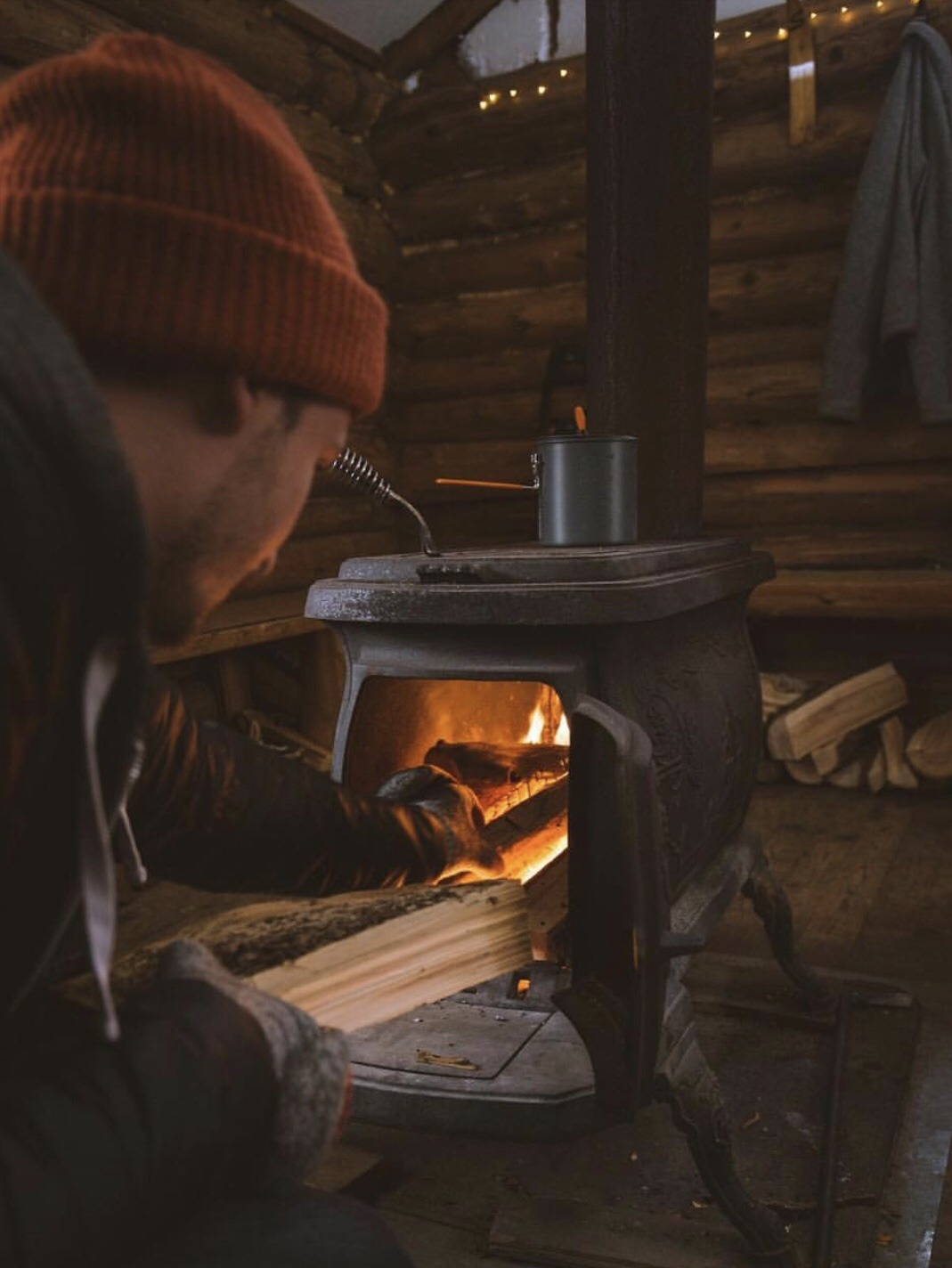 man adding firewood to stove