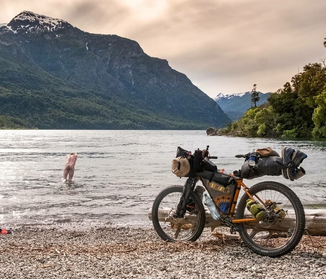 naked man diving into river after long bike ride