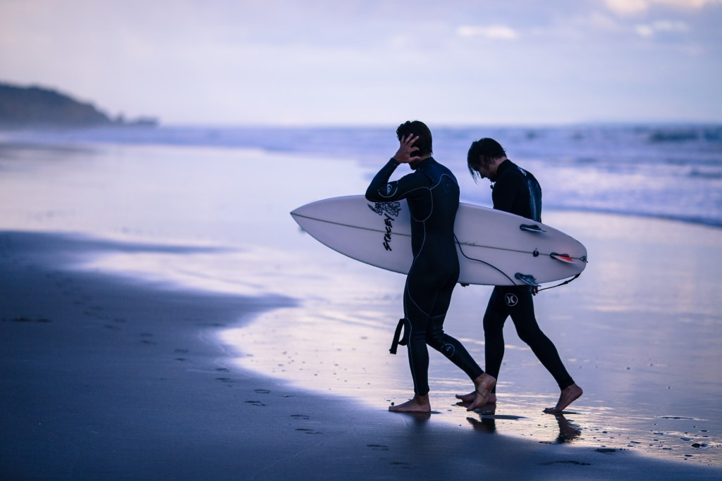 two men with surfboards on beach