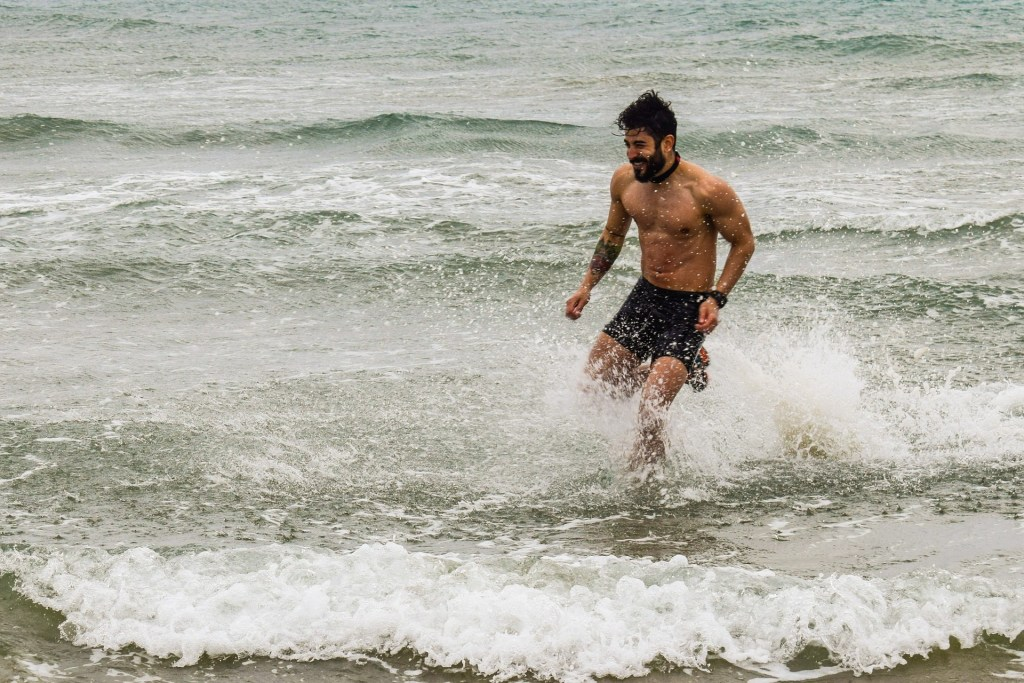fit man running in ocean
