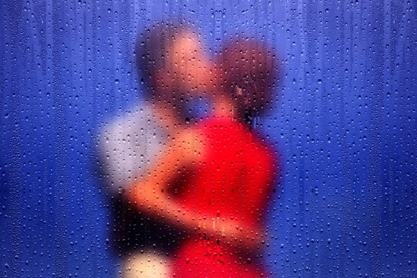 couple kissing behind a wet window