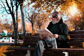 photo of man holding newspaper while sitting on park bench
