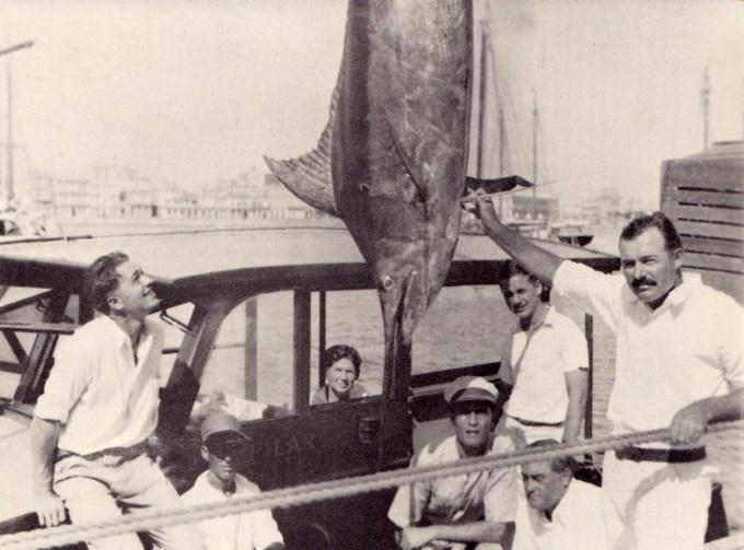 Hemingway shows off a 324-pound blue marlin as Samuelson (far left) admires it.