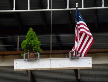 The beam, complete with good-luck symbols – an American flag and fir tree – is hoisted by a crane to the structure.