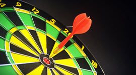 Dart board with a dart stuck in the bulls-eye