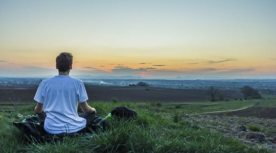 a man in a meditative pose looking across a landscape