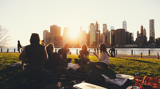 people sitting on grass with a city skyline in the background