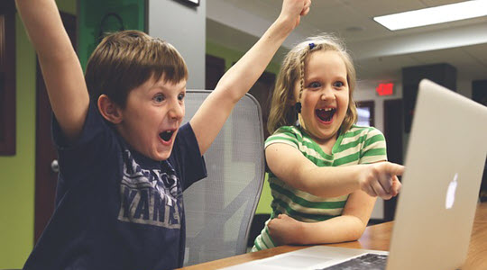 two children celebrating and pointing to a computer screen