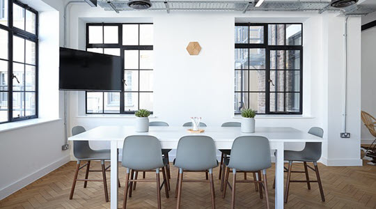 A white table and chairs in a bright boardroom