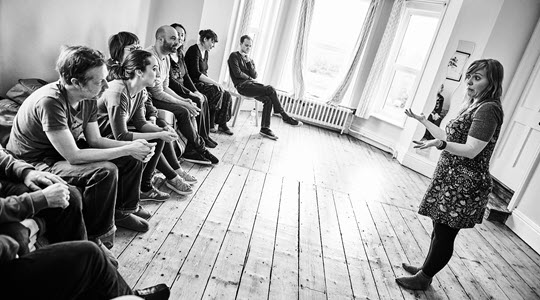A group of people sitting being taught improvisation