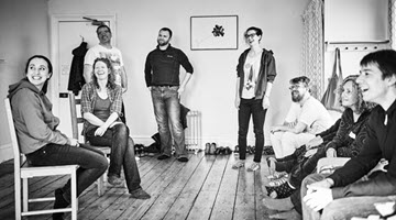 A group of people in an Improv Class looking happy