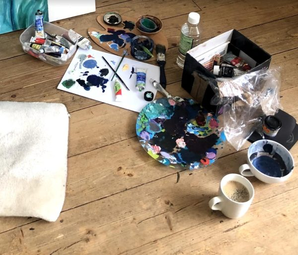 Image of an artists paints and palette on a wooden floor