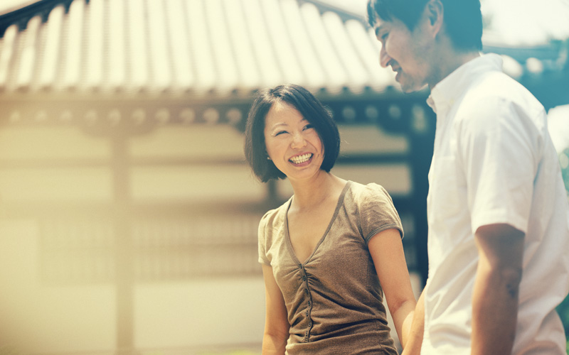 woman and man smiling and walking outside in the sunshine