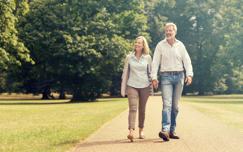 middle aged couple holding hands and walking along a stone path