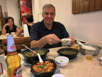 Happy guy surrounded by spicy food. That's the duck blood tofu in foreground.